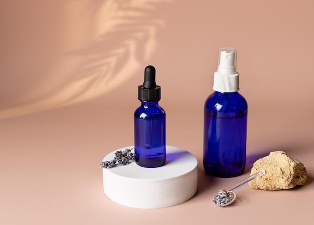 Cosmetisch product in blauwe glazen flessen in wit podium met gedroogde lavendel op lichte koraalachtergrond
