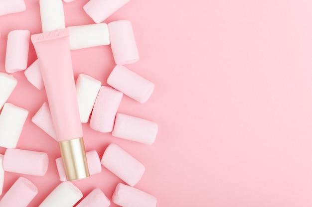 Cosmetisch product in roze verpakking op een pastel achtergrond met kleurrijke snoepjes.