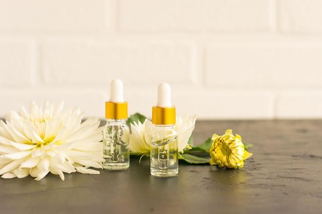 Cosmetisch product in transparante flessen tegen de achtergrond van een witte bakstenen muur en bloemen.