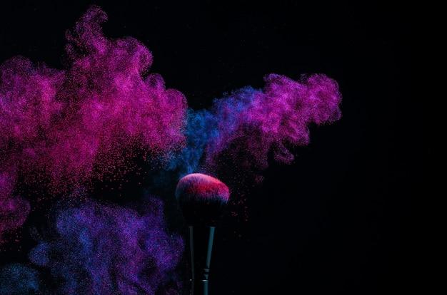 Cosmetische borstels in een helder poederpoeder. kleurrijke explosie onder make-up.