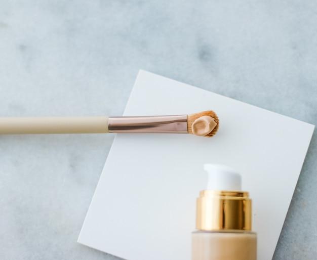 Cosmetische branding glamour en huidverzorging concept make-up foundation fles en contourborstel op mar ...