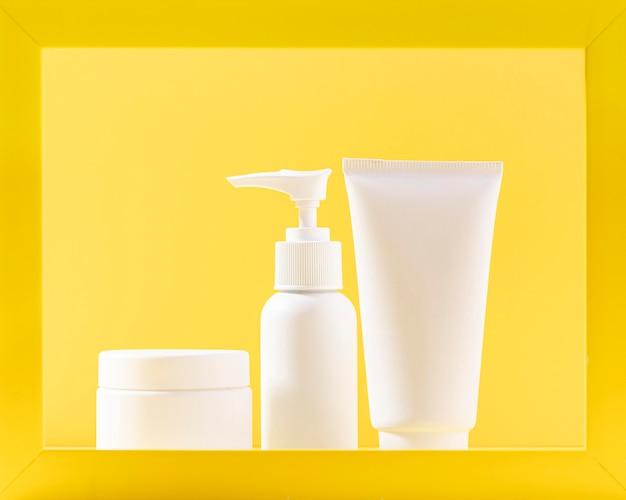 Cosmetische containers met gele achtergrond