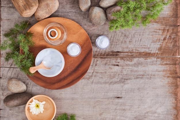Cosmetische crème en verse bladeren op houten tafel achtergrond