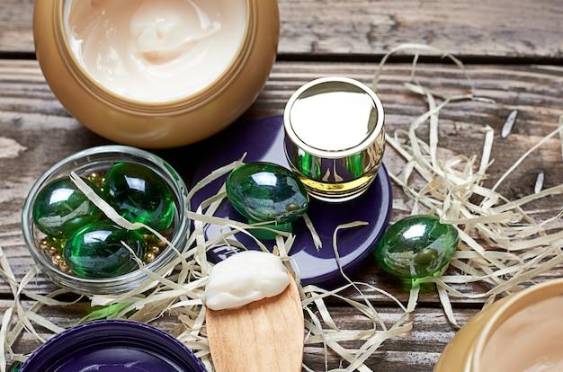 Cosmetische crème in een pot, glazen groene ballen, cosmetische lotion in een glazen pot op een houten tafel