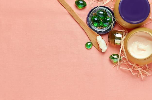 Cosmetische crème in een potje en op een houten lepel met glazen groene kristallen op een scharlakenrode doek. het uitzicht vanaf de top