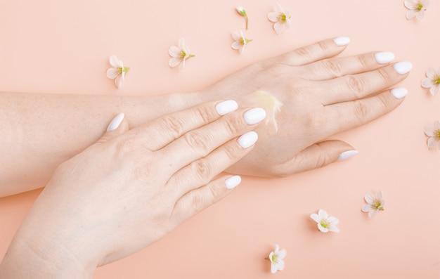 Cosmetische crème op volwassen huid vrouwelijke handen, witte bloemen op perzik kleur tafelblad weergave