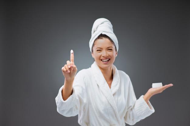 Cosmetische crèmes aanbrengen. een glimlachende en leuke vrouw in een badjas en een handdoek om haar hoofd gewikkeld houdt de crème in haar hand. ze pakte de crème met haar vinger en wees naar voor de camera