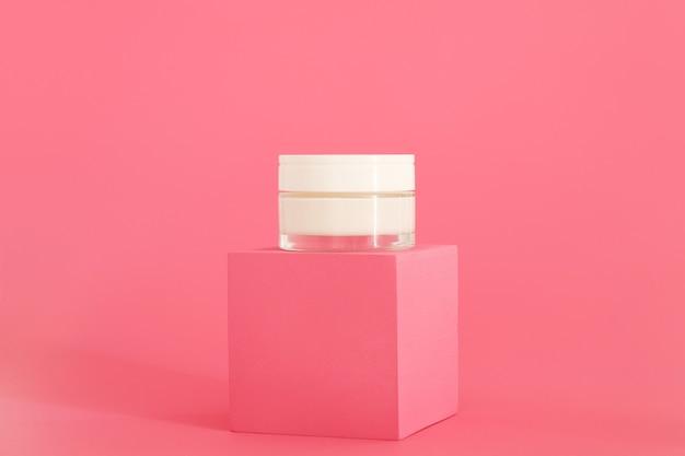 Cosmetische crèmeverpakking die op een roze podium staat. crème presentatie op de roze achtergrond. mock-up.
