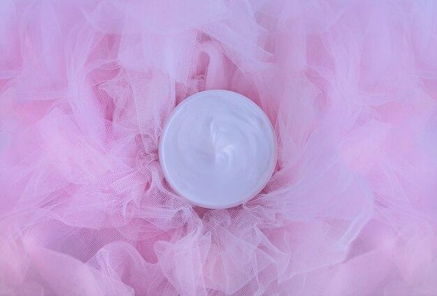 Cosmetische fles crèmelotion op roze tulestof