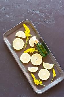 Cosmetische fles met groene glazen pipet met citrusolie op een bord met schijfjes citroen en gele bloemen. bovenaanzicht.