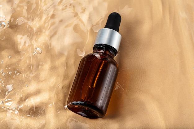 Cosmetische fles met pipet in golvend water