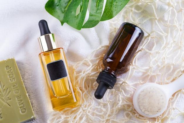 Cosmetische fles met serum en hyaluronzuur, palmblad, olijfzeep en herbruikbare boodschappentassen op een witte handdoek