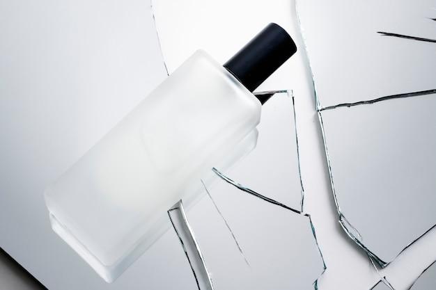 Cosmetische fles op stukjes gebroken verbrijzeld glas