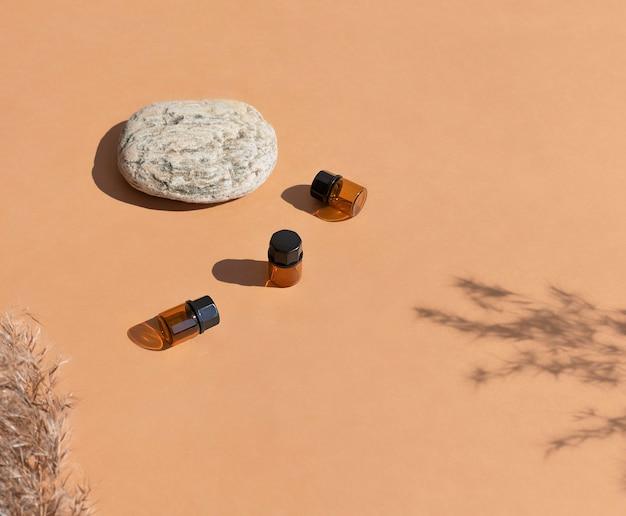 Cosmetische flessen gemaakt van amberkleurig glas met natuurlijke elementen steengras zonlicht