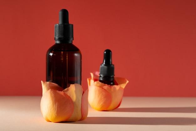 Cosmetische flessen met rozenblaadjes, kopie ruimte