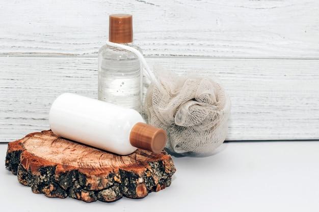 Cosmetische flessen voor badkamer en washandje op houten ondergrond.