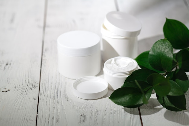 Cosmetische flessencontainers met groene kruidenbladeren, blanco labelpakket voor brandingmodel, natuurlijk organisch schoonheidsproductconcept