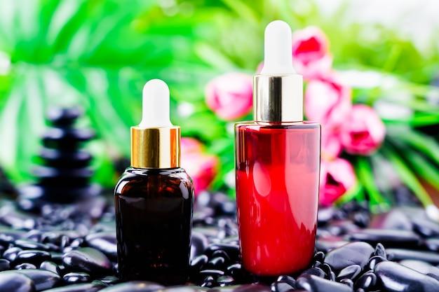 Cosmetische glazen fles voor etherische oliën op zwarte steen tegen de achtergrond van een bloei