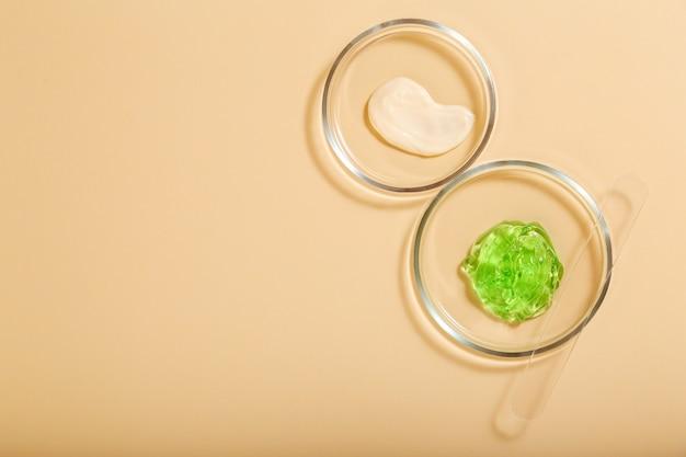 Cosmetische huidverzorgingsproducten in petrischalen op beige achtergrond. aloë gel, vochtinbrengende crème natuurlijke cosmetica voor cosmetologie in laboratoriumglaswerk. plat leggen met kopieerruimte.