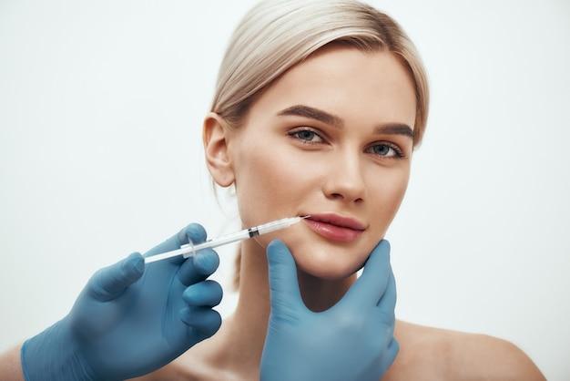 Cosmetische injectie jonge mooie vrouw die naar de camera kijkt en glimlacht terwijl artsen een hand maken