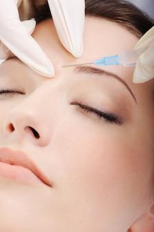 Cosmetische injectie van botox aan het mooie vrouwelijke gezicht - close-upportret