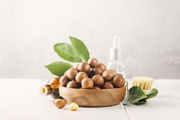 Cosmetische macadamia-notenolie op een grijze betonnen tafel.