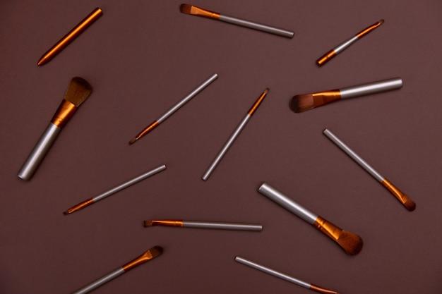 Cosmetische make-up borstels op een bruine achtergrond kopieer de ruimte cosmetische schoonheid concept