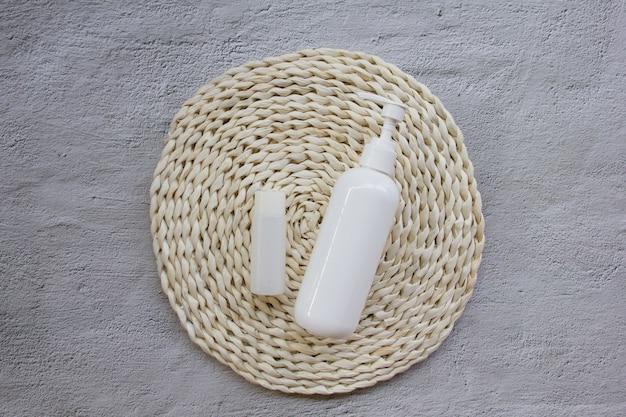 Cosmetische mock-up fles op rieten pad op beton
