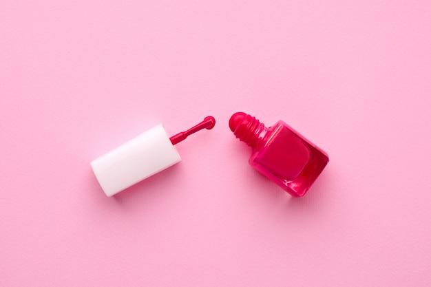 Cosmetische nagellak roze kleur met penseel op roze