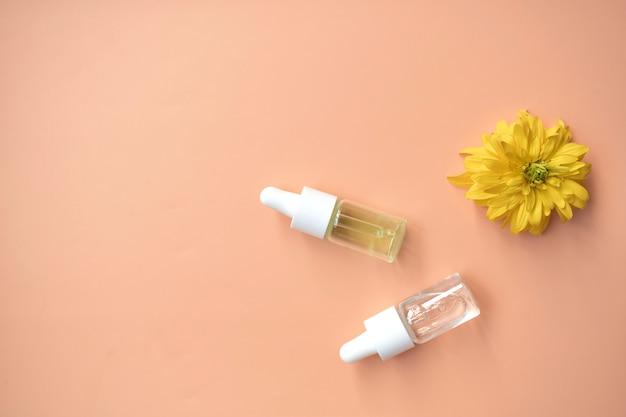 Cosmetische olie in een flesje met een pipet voor het gezicht en lichaam op een natuurlijke ondergrond met een decor in de vorm van een natuursteen. ruimte voor tekst.