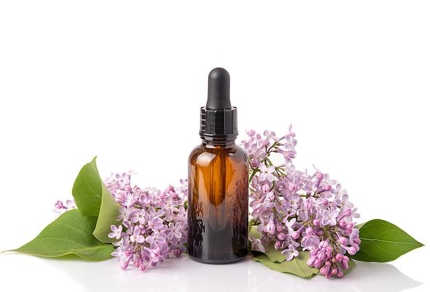 Cosmetische olie in lila bloemen. cosmetica voor lichaams- en gezichtshuidverzorging. op witte achtergrond. isoleren.