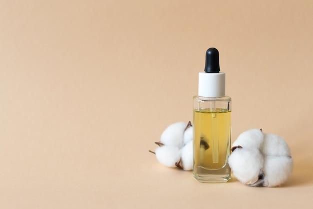 Cosmetische olie voor gezicht en lichaam, flesje met olie op beige achtergrond, plaats voor tekst. hoge kwaliteit foto