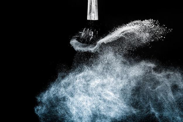 Cosmetische penseel met blauwe cosmetische poederstrooiing voor visagist en grafisch ontwerp in zwarte muur