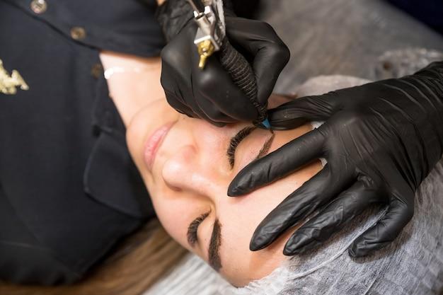 Cosmetische procedures voor de behandeling van wenkbrauwen. microblading in de schoonheidssalon. professionele cosmetologie. het proces van het aanbrengen van het pigment, het vormen van wenkbrauwen. permanente make-up wenkbrauwen, tatoeage