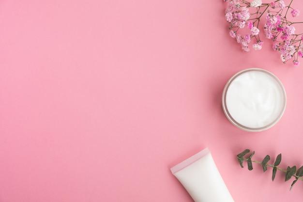 Cosmetische producten, bloemen en eucalyptusbladeren op roze.