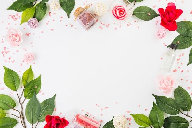 Cosmetische producten en bladeren die kader op witte oppervlakte vormen