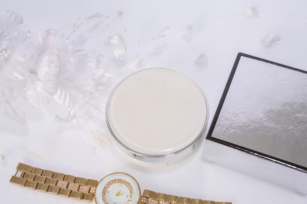 Cosmetische producten en bloemen op wit