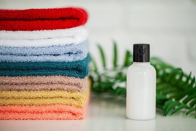 Cosmetische producten en katoenen handdoeken op witte houten tafel in schoonheidssalon