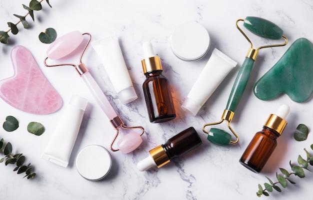 Cosmetische producten, etherische oliën, crèmebuizen en gezichtsroller op een marmeren muur