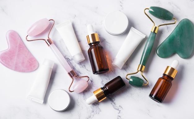 Cosmetische producten, etherische oliën, crèmebuizen en gezichtsroller op een marmeren tafel