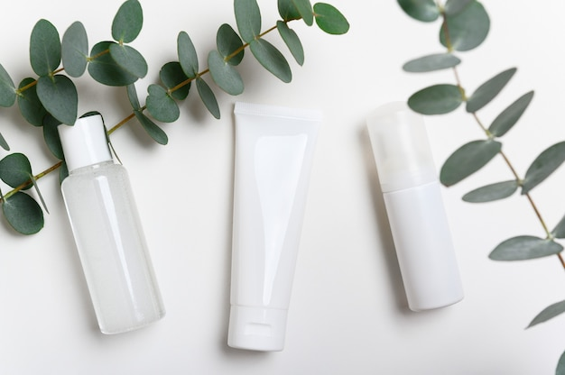 Cosmetische producten flessen op witte achtergrond bovenaanzicht. gezichtscrème, masker.