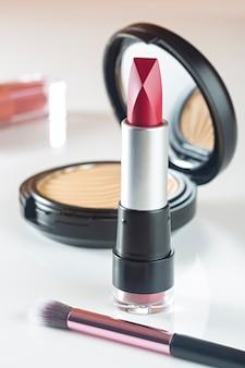 Cosmetische producten lippenstift, poeder op witte tafel.