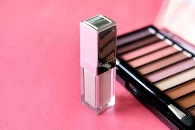 Cosmetische producten, oogschaduwpalet, lipgloss op levendige roze achtergrond. schoonheid concept.