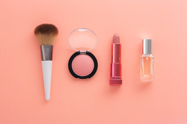 Cosmetische producten op lichte koraalachtergrond