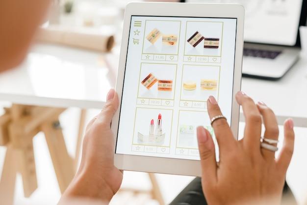 Cosmetische producten op touchpad-display en vrouwelijke hand die door het spul scrolt tijdens het kiezen van lippenstift en zeep