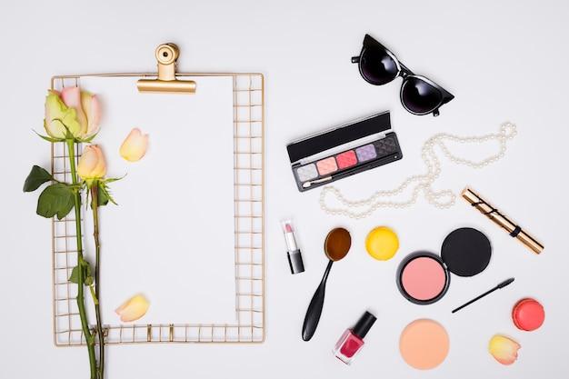 Cosmetische producten; roos op wit papier over het klembord geïsoleerd tegen een witte achtergrond