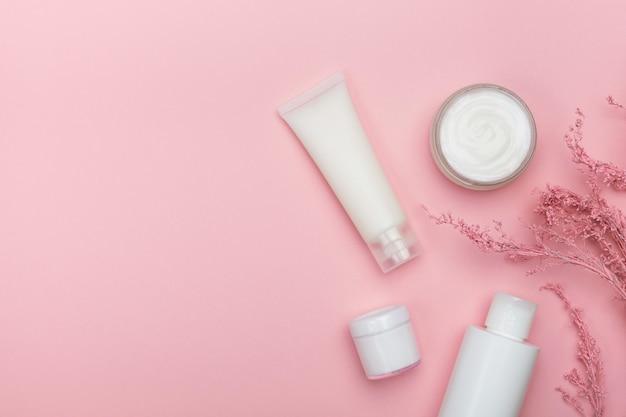 Cosmetische producten, tak van bloemen op roze tafel. natuurlijke cosmetica en huidverzorging