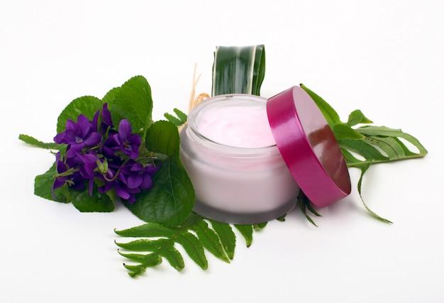 Cosmetische roze crème met kruiden en bloemen