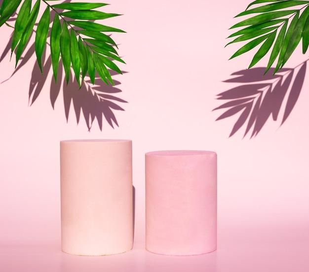 Cosmetische roze podia en groen blad met schaduw op roze