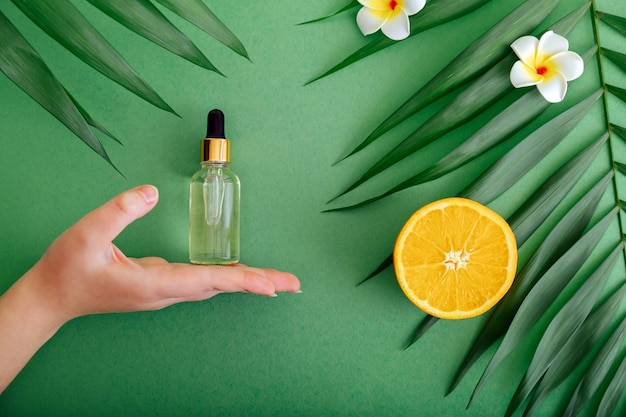 Cosmetische serum vitamine c in glazen fles met pipet druppelaar in vrouwelijke hand. essentiële olie van sinaasappel